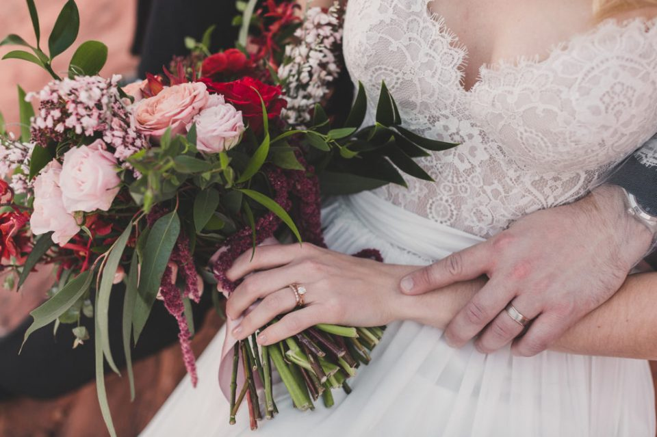 close up of bride's hand on bouquet with red flowers