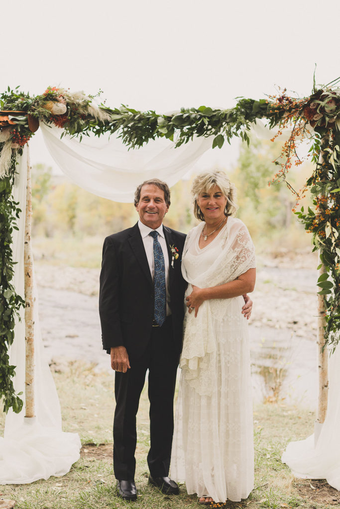 bride and groom pose by floral arbor along river at Freestone Lodge