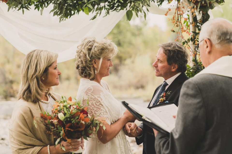 bride and groom exchange vows during fall wedding ceremony