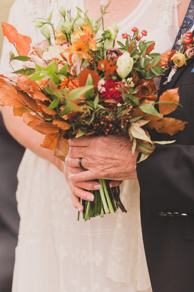 groom holds bride's bouquet with her