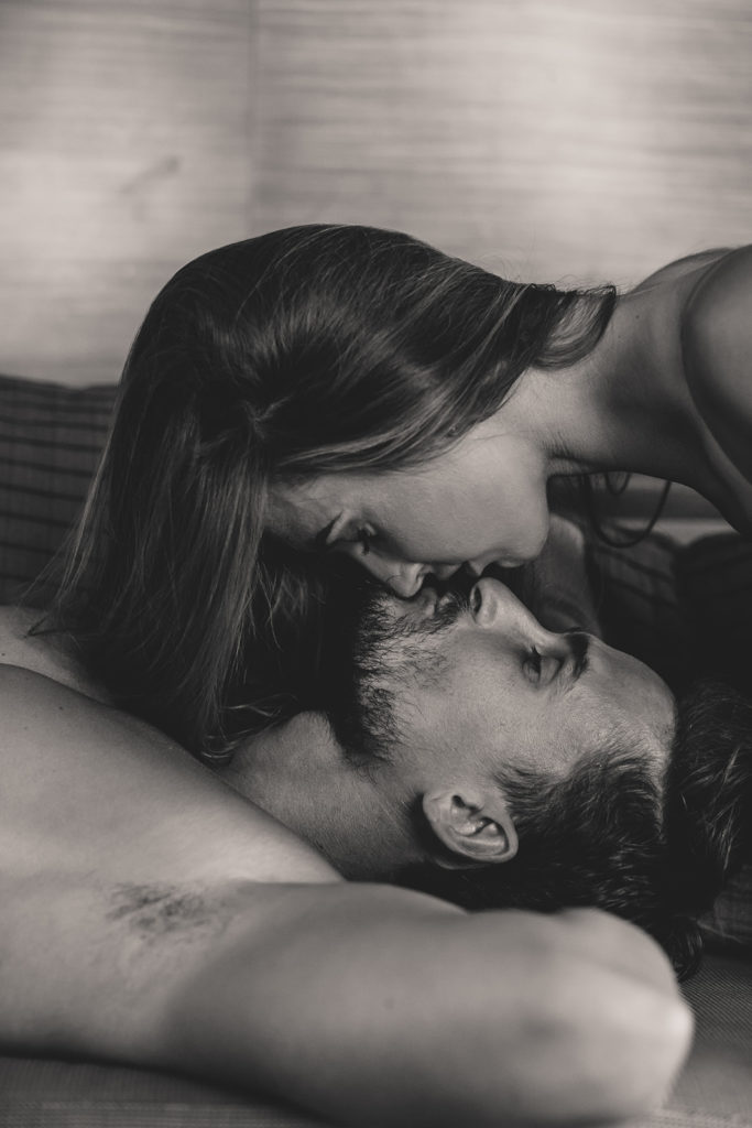 couple kisses during sexy couples boudoir session