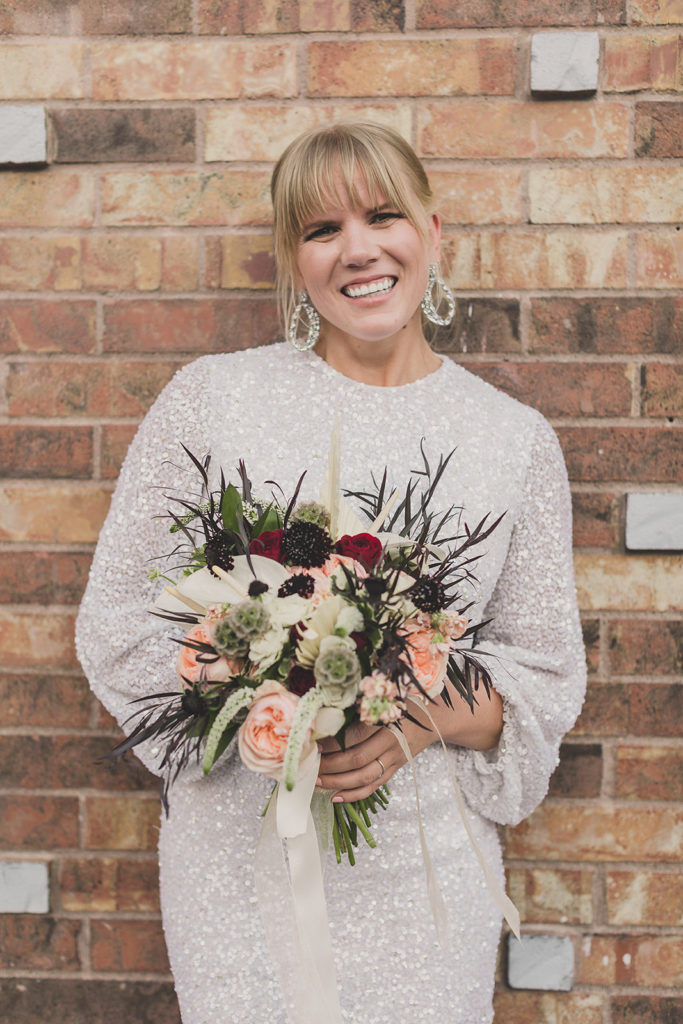 bride holds red, pink, and white bouquet by brick wall in Las Vegas