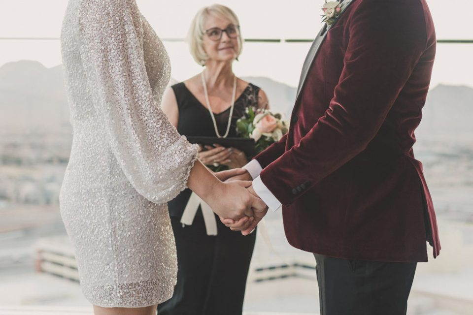 couple holds hands during wedding ceremony