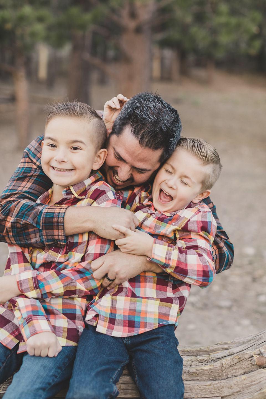 boys hug dad during family photos