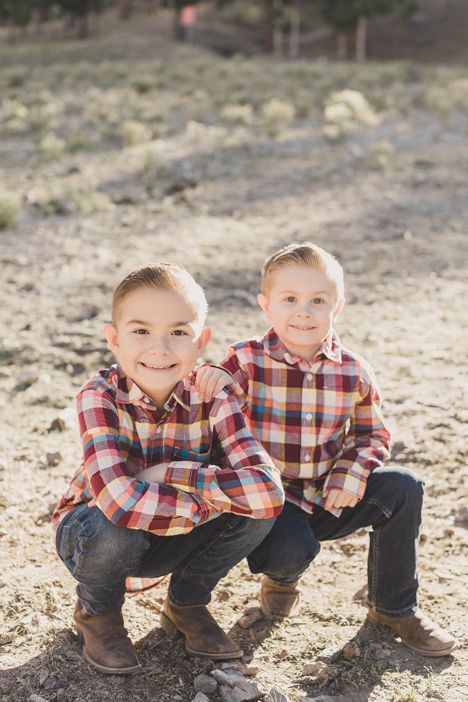 boys in red plaid shirts sit in dirt during Las Vegas family photos