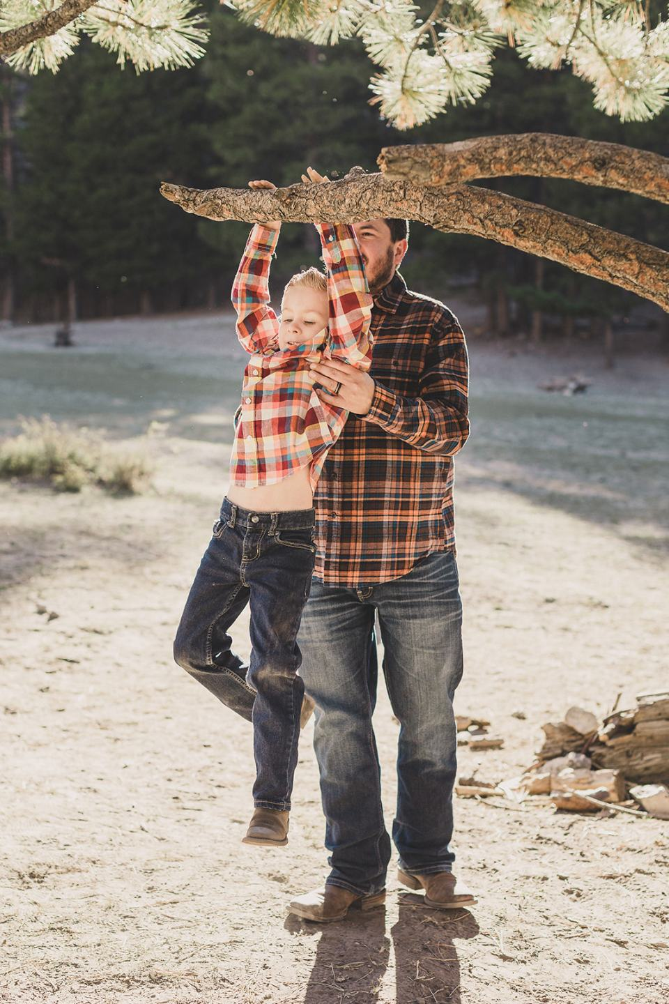 dad lifts son onto tree branch