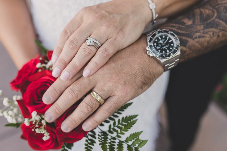 bride and groom hold hands with wedding rings on bouquet