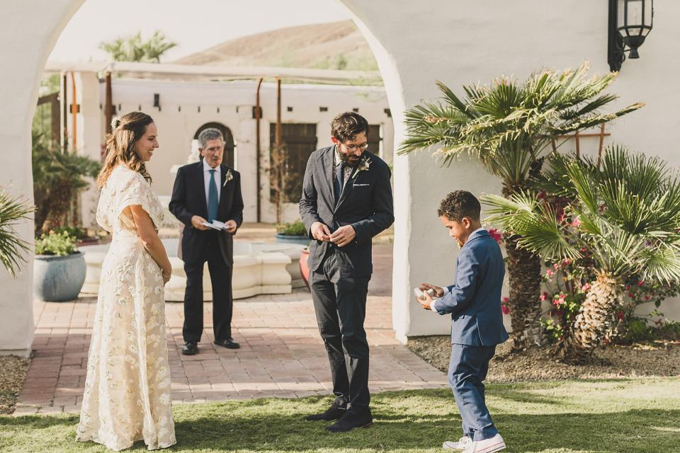 bride and groom get rings from ring bearer