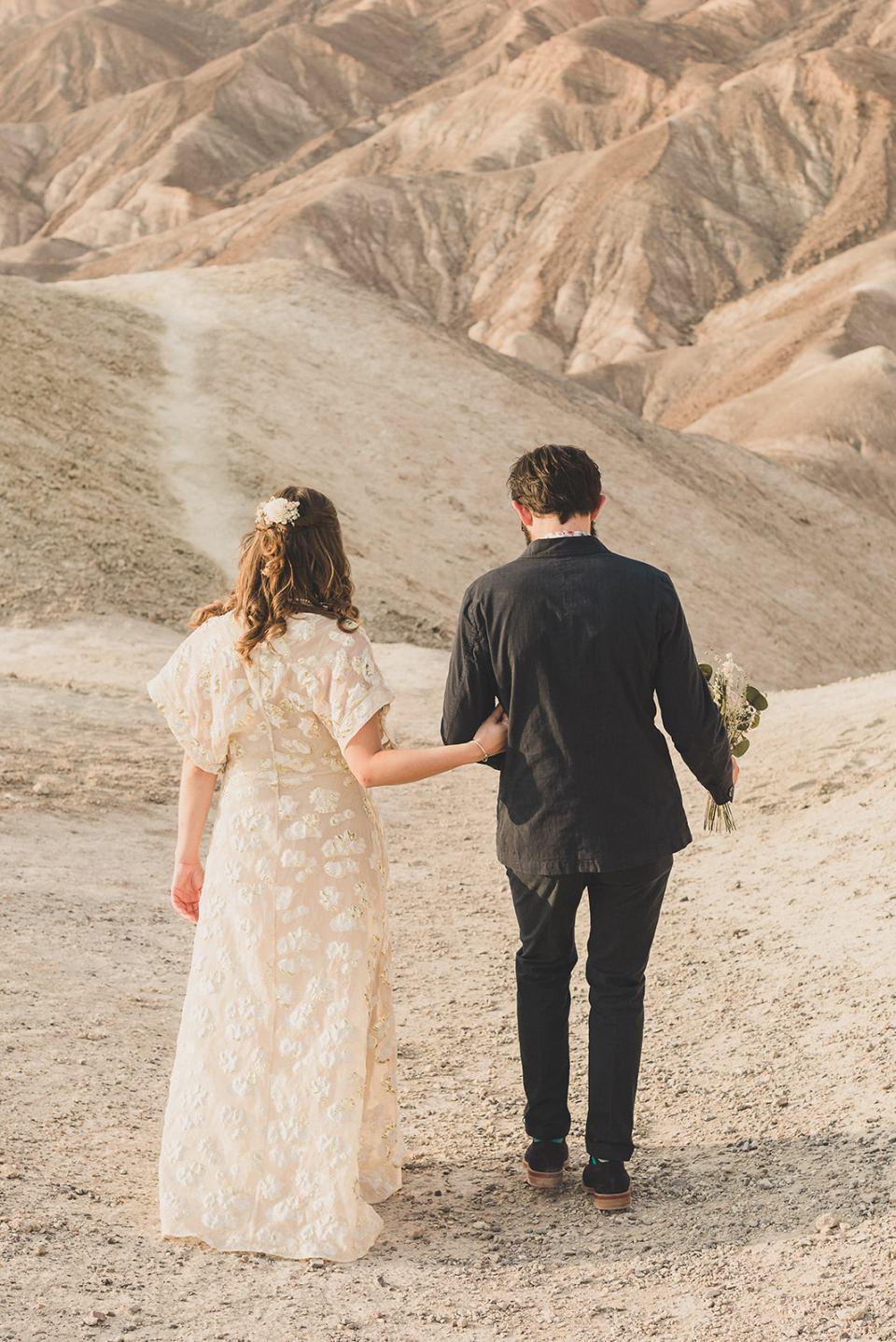 bride and groom walk through hills at Zabriskie Point
