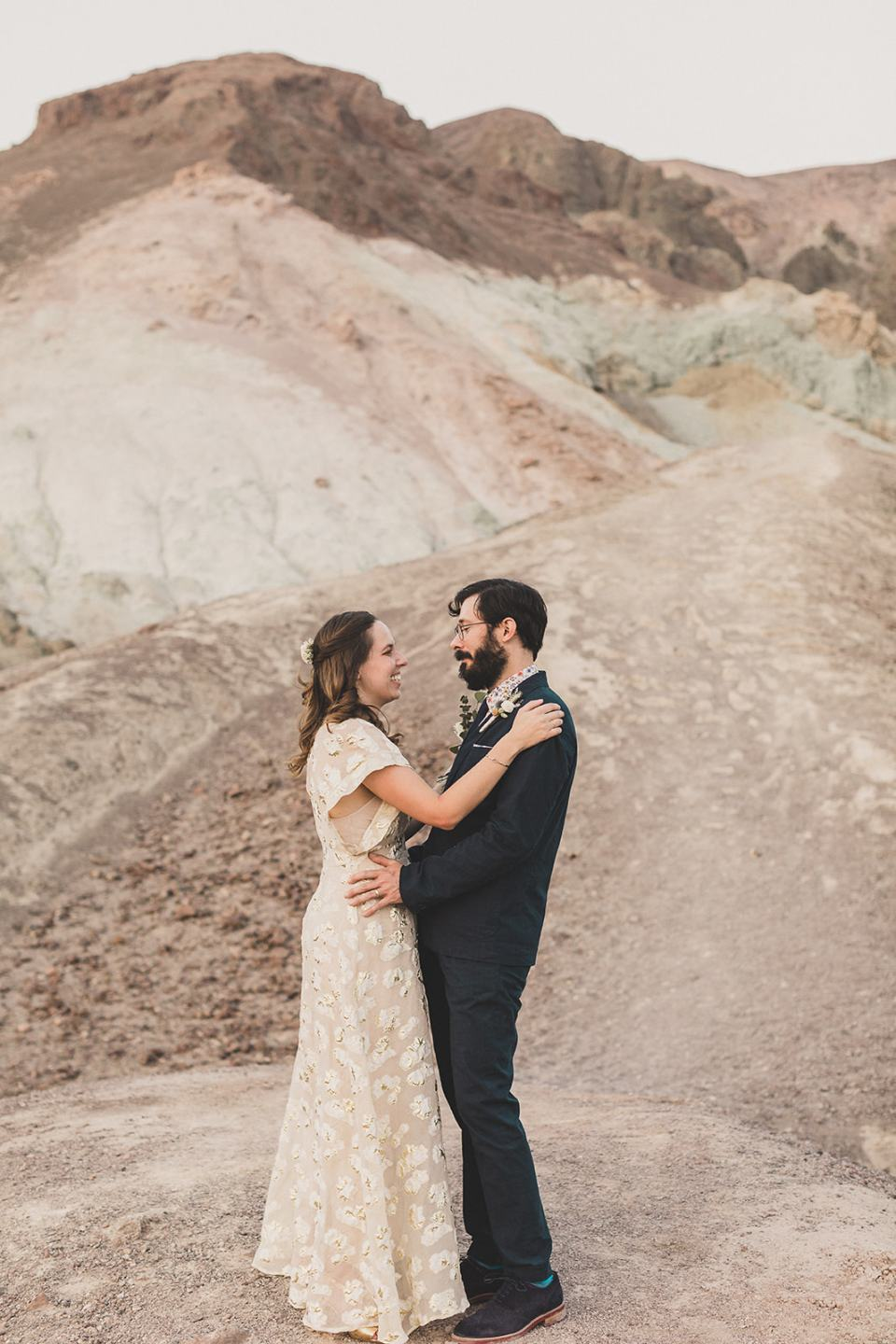 newlyweds dance in front of hills at Zabriskie Point