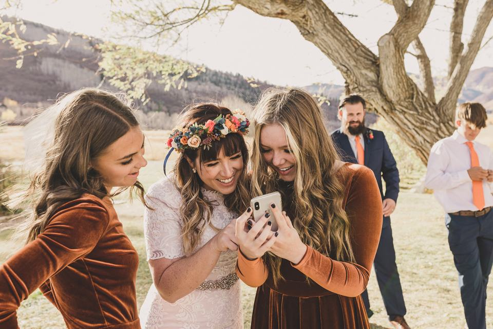 mom looks at phone after photo with daughters