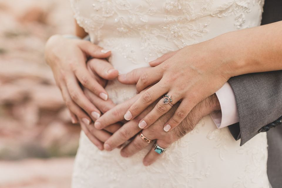 newlyweds hold hands on bride's dress