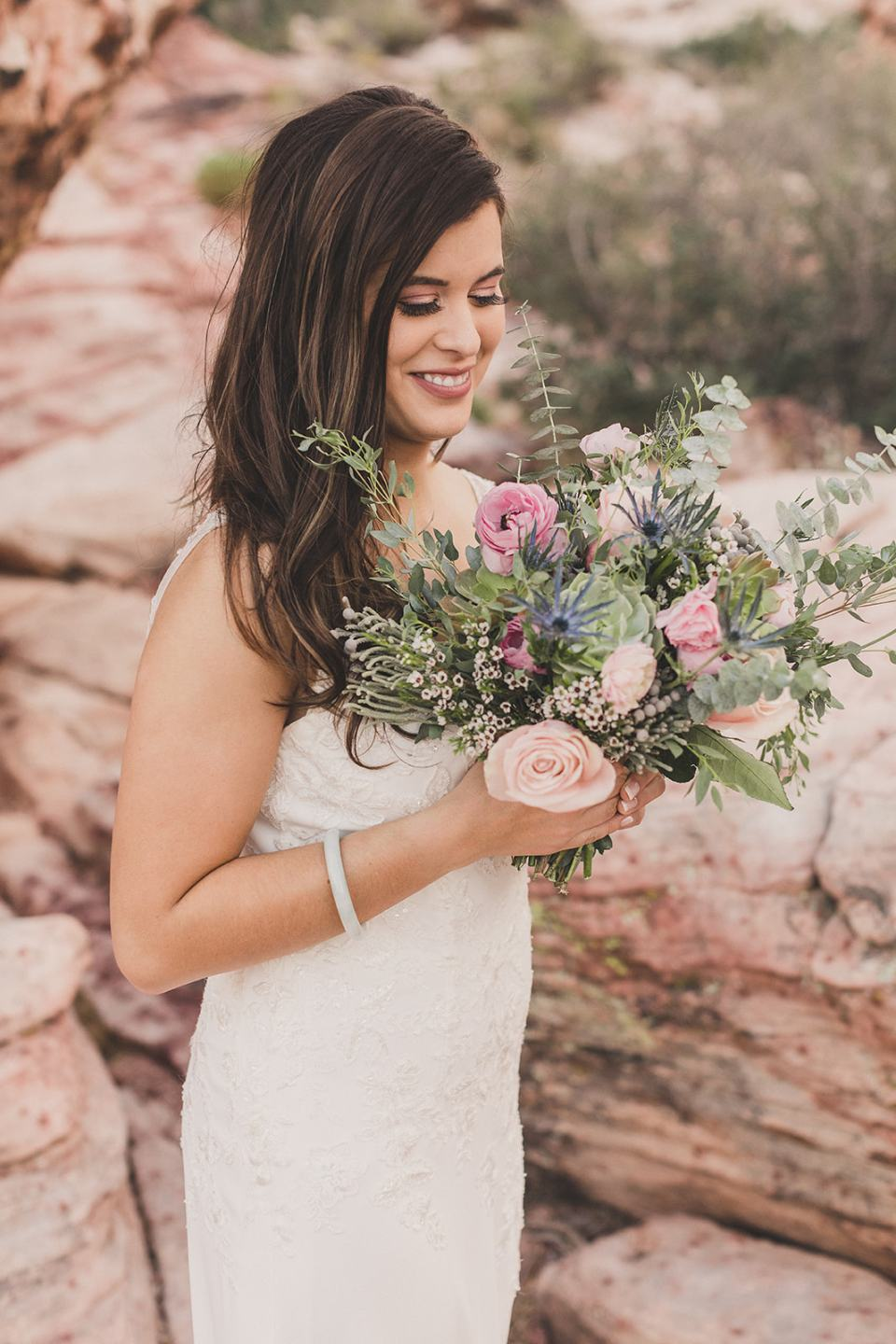bride looks at bouquet during portraits in Las Vegas