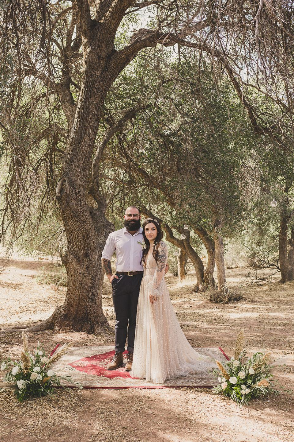 newlyweds pose on ceremony site at Spring Mountain Ranch