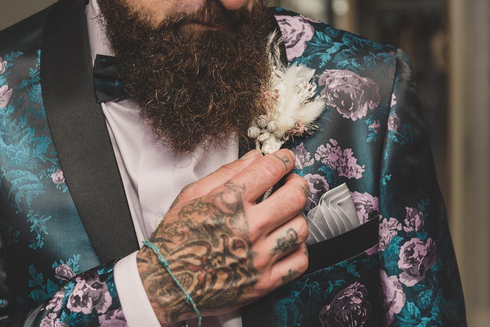 groom adjusts simple boutonnière on custom jacket