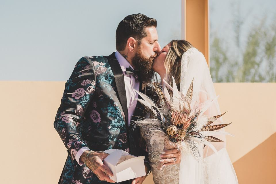 bride and groom kiss after butterfly release after Las Vegas wedding ceremony