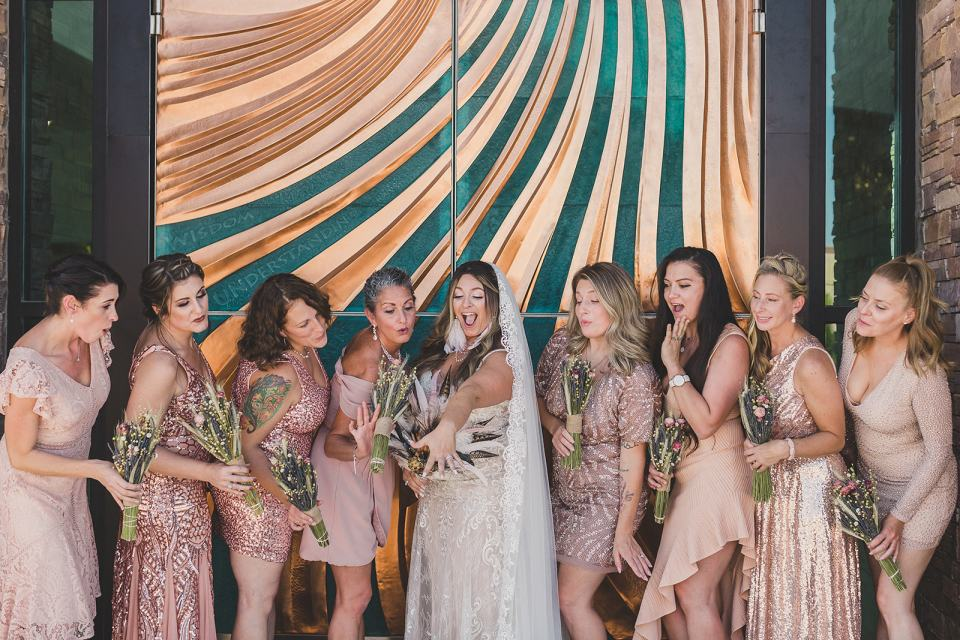 bride shows off wedding ring to bridal party