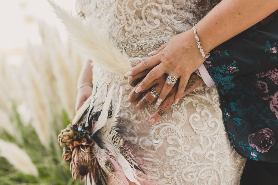 bride and groom hold hands on bride's hip
