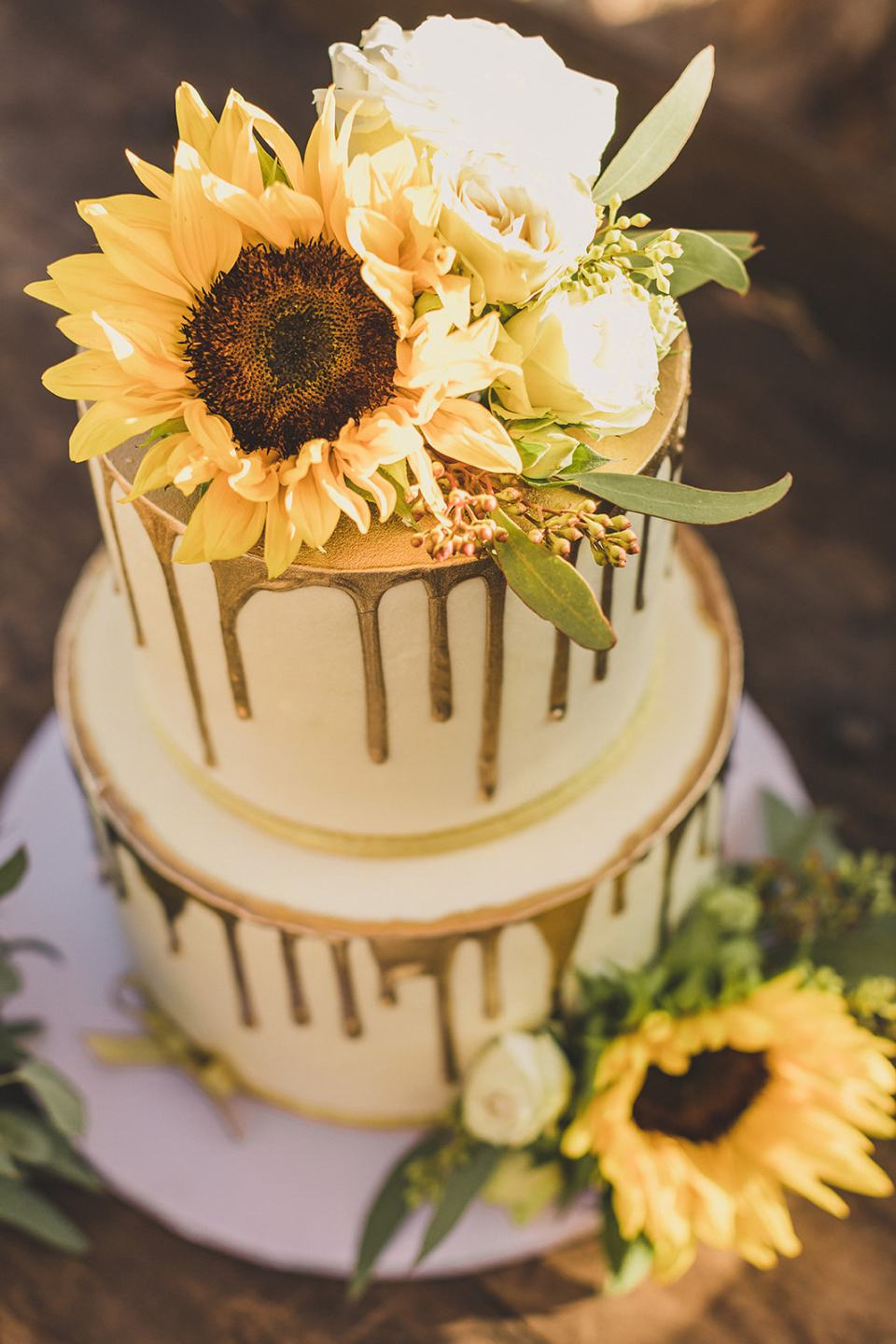wedding cake with sunflowers and drip gold icing