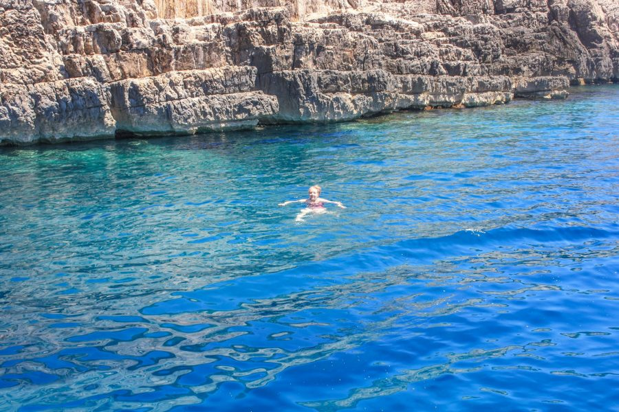 A woman swimming in the blue water at Odysseus Cave, Mljet Island