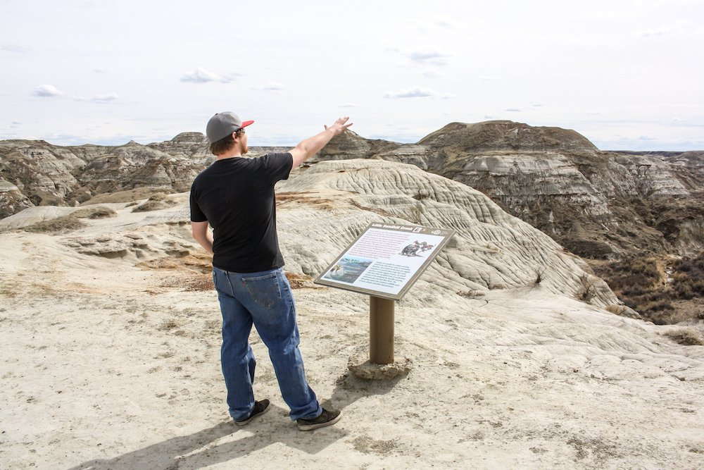 A man points into the canyon at dinosaur provincial park, with a plaque in front of him explaining the view