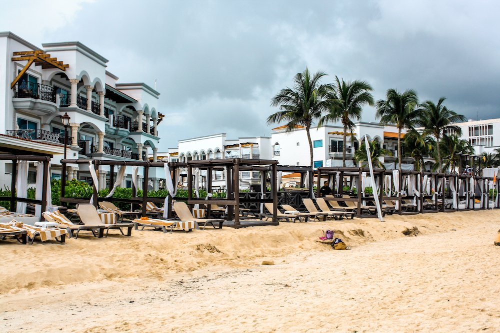 A downtown beach in Playa del Carmen with hotels and lounger chairs.