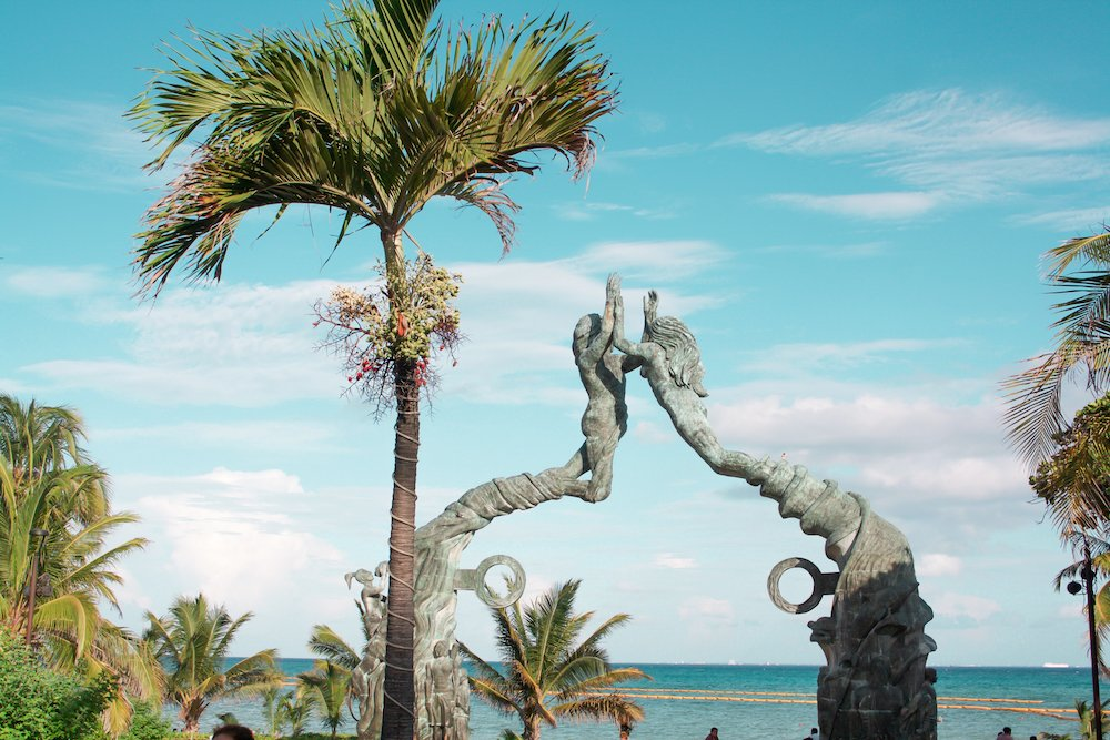 Statue of two mermaids in downtown playa del carmen with the ocean in the background.