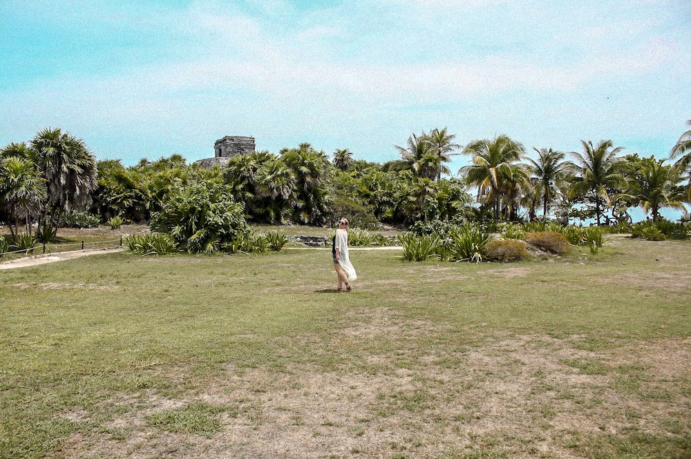 Taylor in front of the Tulum ruins with palm trees, a blue sky, and lots of green grass