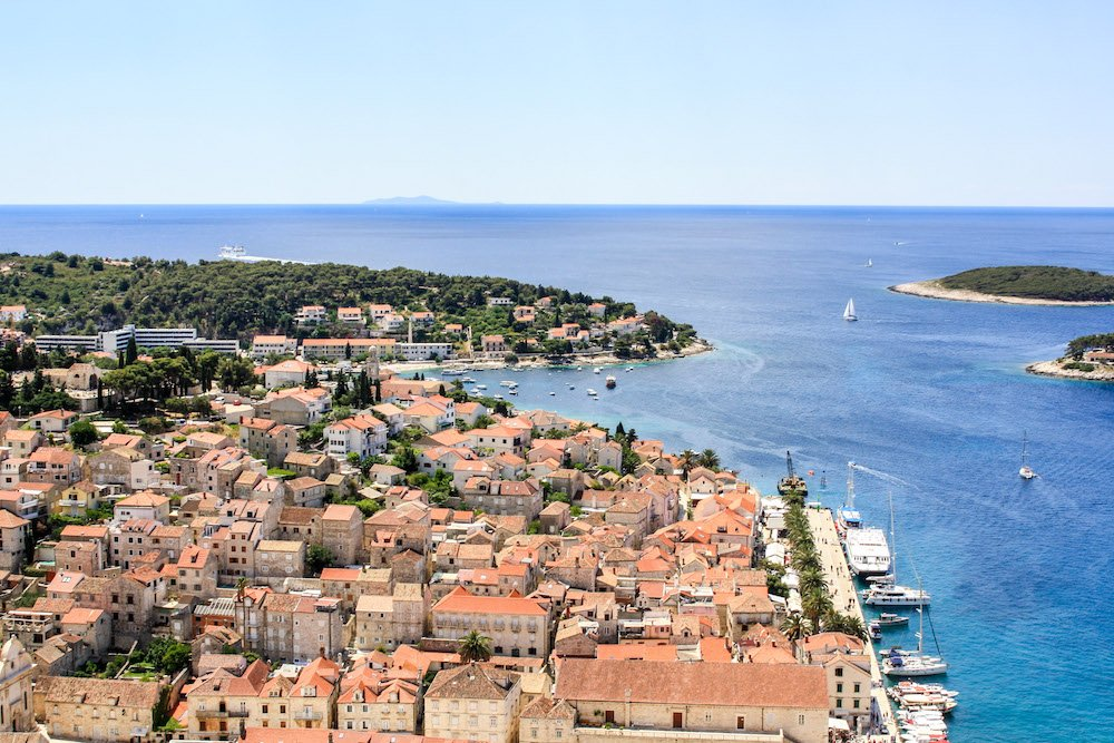 An overhead shot of Hvar, Croatia with terracotta roofed buildings, the ocean, and islands