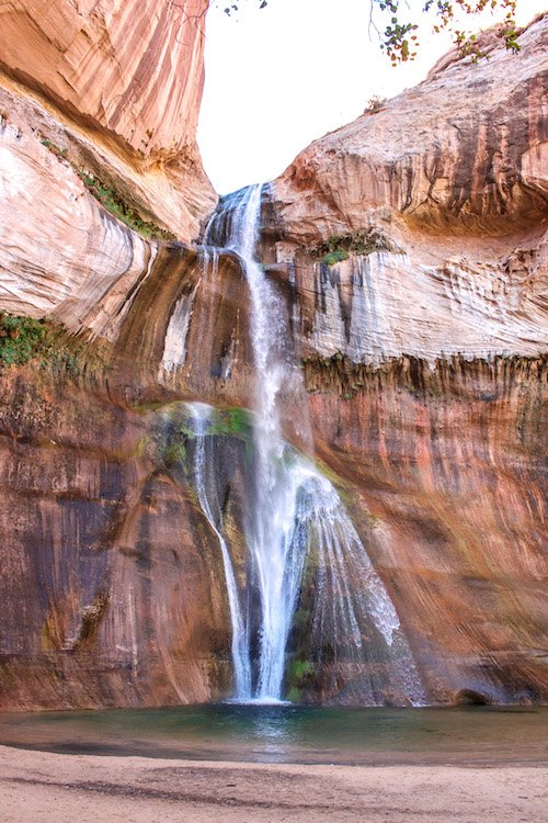 Lower Calf Creek falls surrounded by red sandstone in Grand Staircase Escalante, Utah