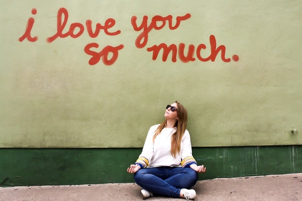 """Sitting in front of grafitti that says """"i love you so much"""" in Austin, Texas"""