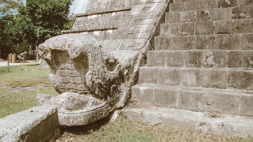 An ancient carved snake head juts out of ruins of Chichen Itza, Mexico