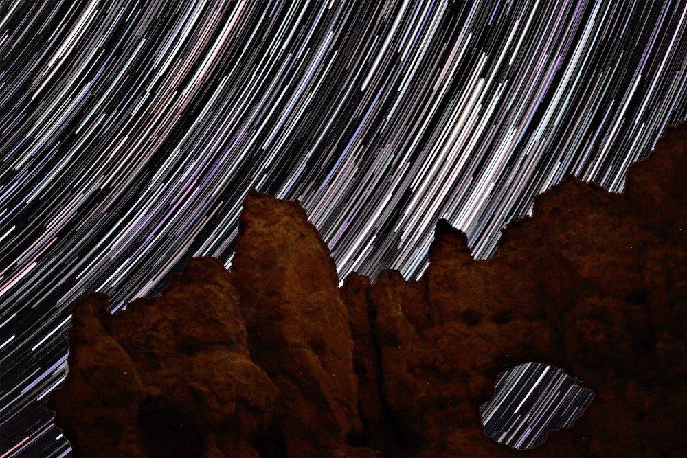 Stars swirl behind hoodoos at night in Bryce Canyon National Park, Utah