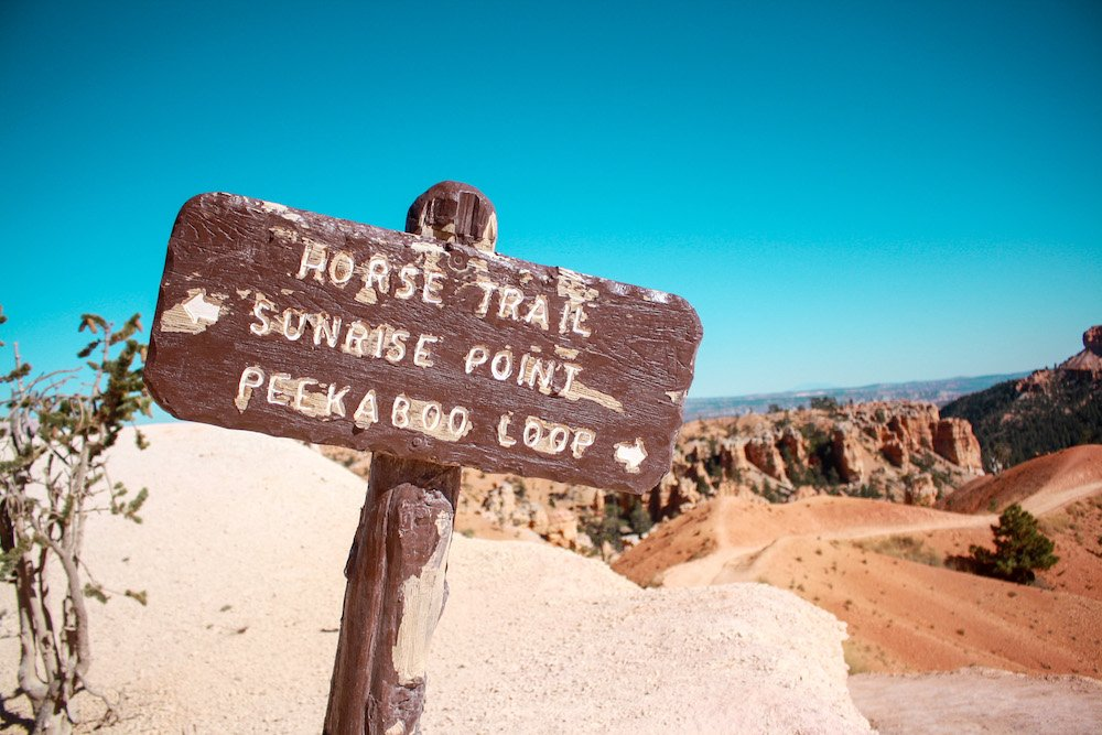 """A sign that says """"horse trail, sunrise point, and peekaboo loop"""" with hoodoos in the background at Bryce Canyon National Park"""