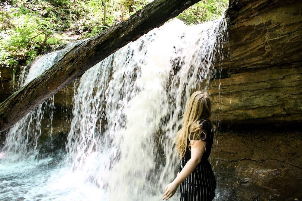 Taylor stands in front of a waterfall in Tioga Trail, Kentucky