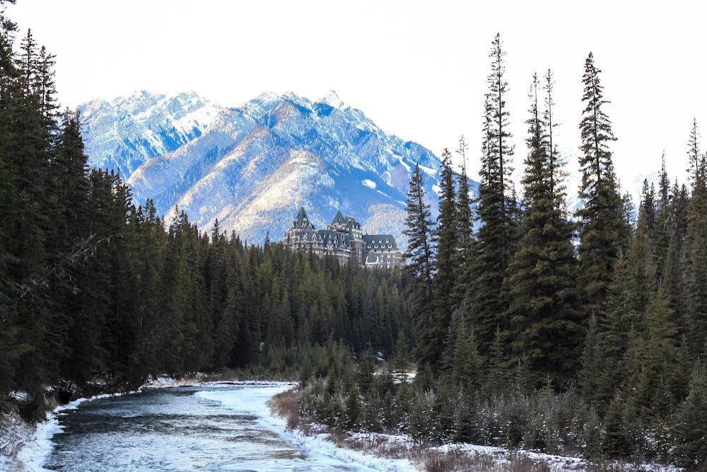 Fairmont Banff Castle surrounded by mountains, green trees, and a rushing river with snow