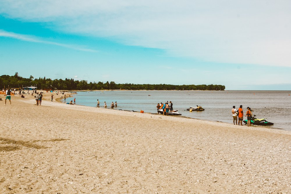People wade in the shallow waters along Gimli Beach under blue skies in Manitoba Canada