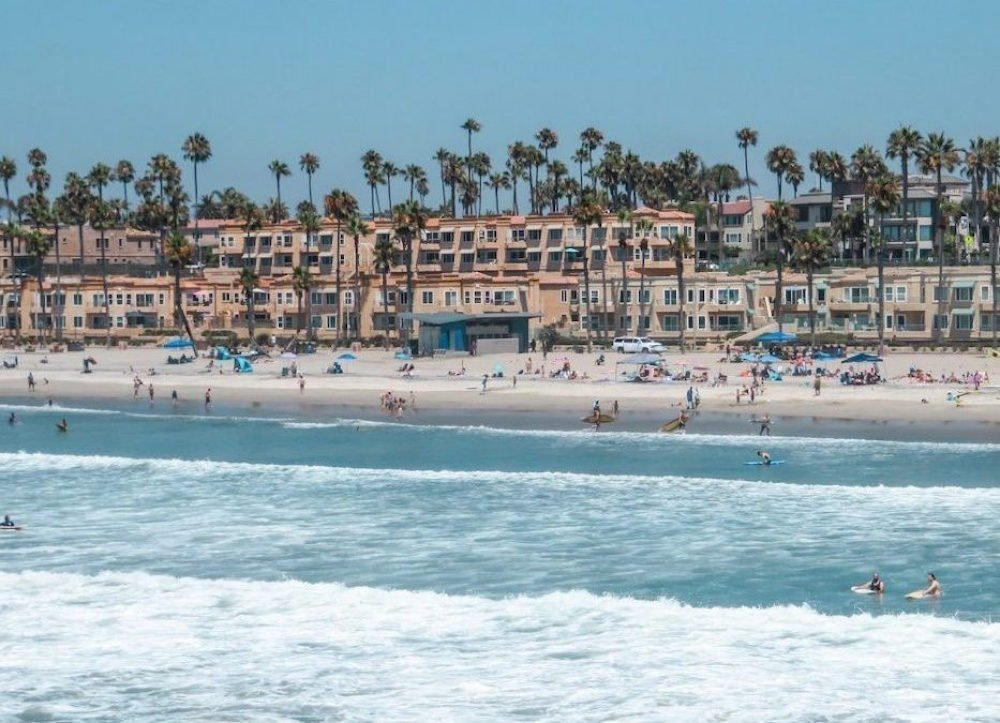 Surfers in the water in front of tan colored houses in Oceanside, California