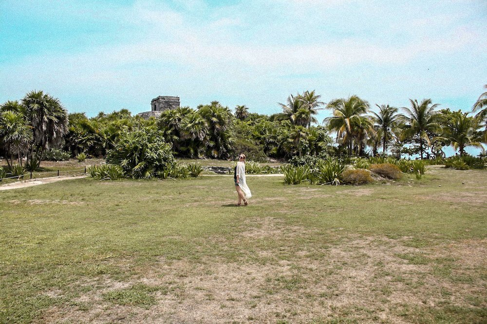 Taylor stands in front of the Tulum ruins and palm trees in Tulum, Mexico