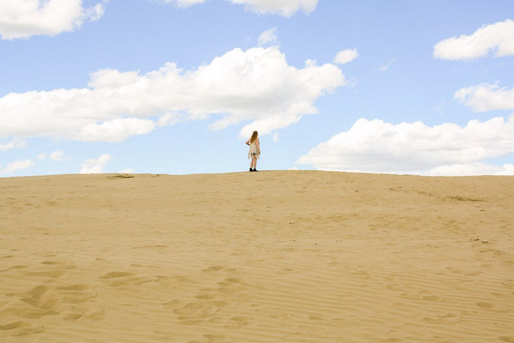 Taylor stands on a tan colored sand dune in the great sand hills of saskatchewan