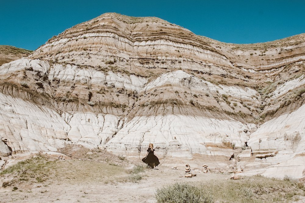 Taylor stands among the multi-layered rock at Drumheller, Alberta