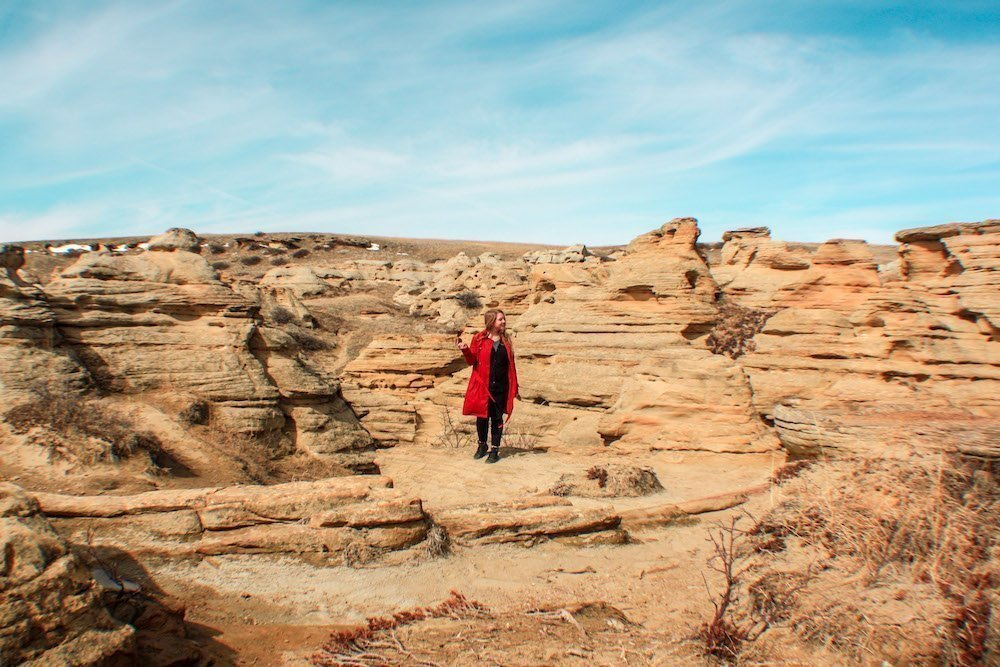 Taylor stands amongst red rock hoodoos in Writing on Stone provincial park in Alberta
