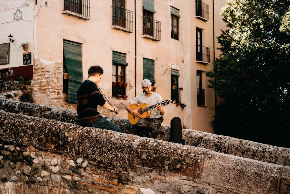 Two men play musical instruments in downtown Granada, Spain