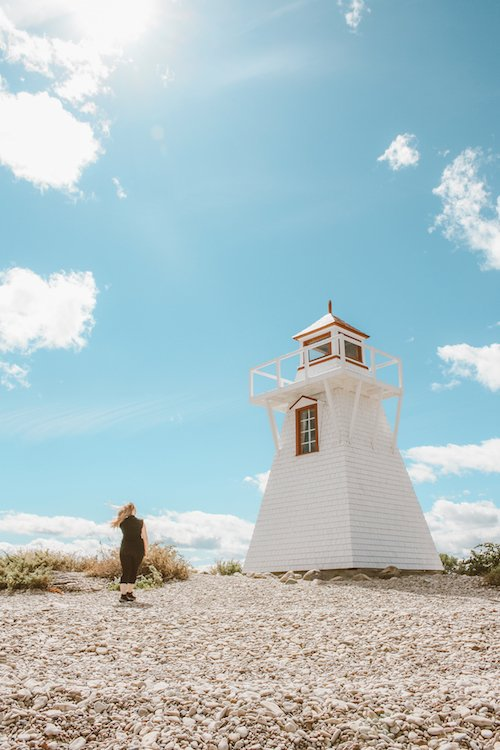 Taylor stands near a lighthouse in Hecla Grindstone Provincial Park in Manitoba Canada