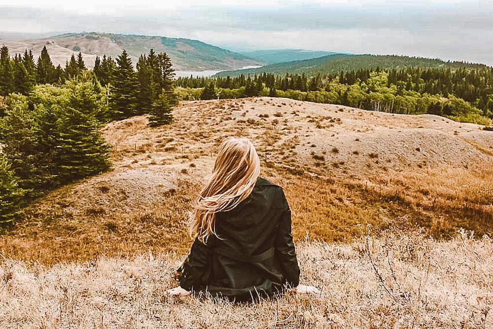Taylor sits with her back to the camera as she looks out over Cypress Hills Interprovincial Park in Alberta with evergreen trees and a lake in the background