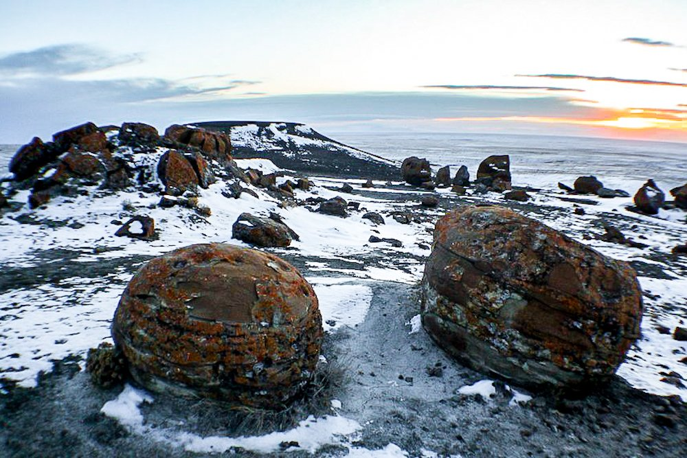 Red Rock Coulee at sunset in Alberta with two big round rocks in the foreground