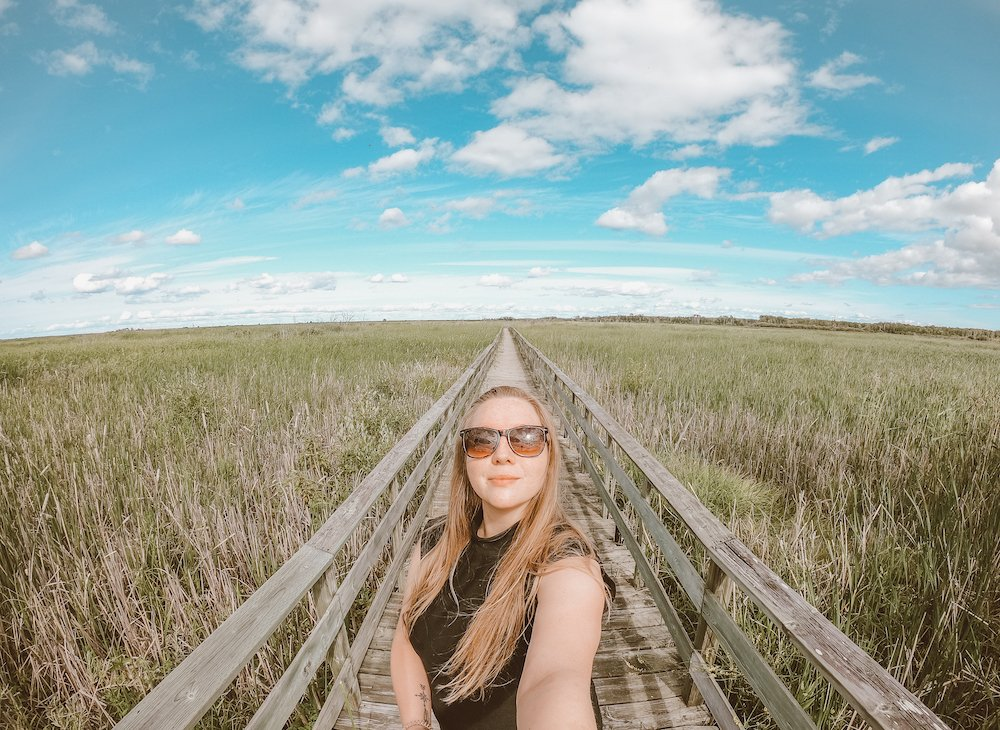 Taylor takes a selfie in Hecla/Grindstone Provincial Park in Manitoba. A boardwalk stretches behind her with tall grass surrounding.