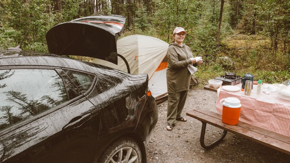 Rita looks at the camera standing between a black car, tent, and picnic table with various camping supplies on it.