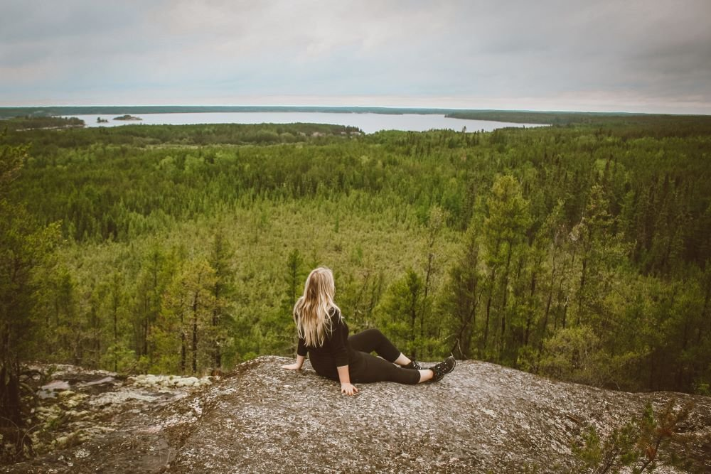 Taylor sits on a precambrian rock looking out over boreal forest and a lake in Nopiming Provincial Park, Manitoba