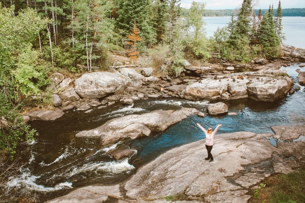 Taylor stands next to Tulabi falls with her arms up in the air. The scene depicts rushing water, green and orange trees, and Tulabi lake.